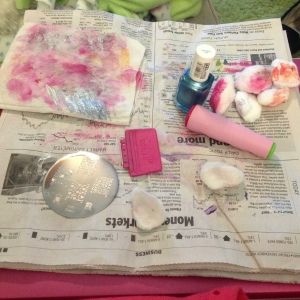 Here is your work station. From mostly left to right you see my well-used paper towel,  my stamping plate, my scraper, a couple remover-soaked cotton balls, my stamper and the polish I'm using for this design Essie Blue Rhapsody. All of this sits on a small stack of newspaper to protect my work surface which happens to be my laptop.